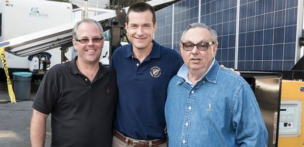 """Jason Bateman on the movie set of """"Bad Words"""", standing in front of a mobile solar trailer."""