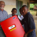 Unboxing the solar inverter: Karsten Riggert with Tanzanian students