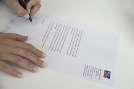 SMA Australia's Lucy Clayton signing her letter to local MP