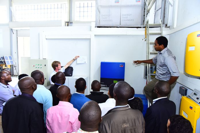 Engineer Evan Kimani explains the SMA inverter to trainees at the SERC Lab at Strathmore University