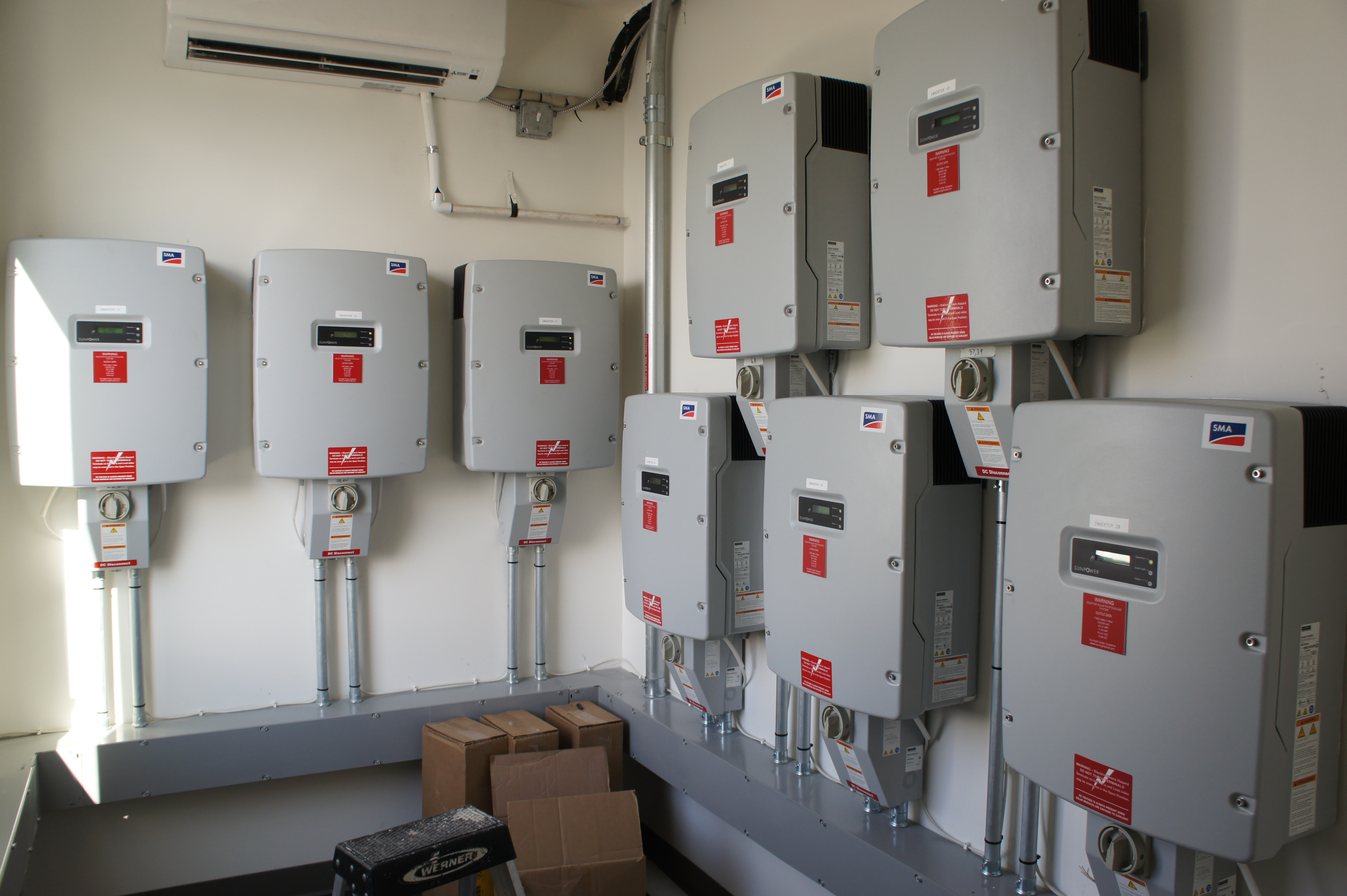 The complex's rooftop modules feed DC power into Sunny Boy 7000-US inverters mounted inside a climate-controlled electrical room