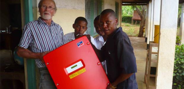 Lehrer Karsten Riggert mit tansanischen Schülern beim Auspacken eines Sunny Mini Centrals