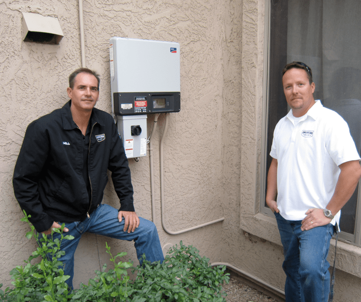 American Solar's Will Herndon and Jeremy Lippens after routing the secure power supply outlet inside the home.