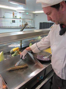 Fleisch anbraten mit Wok und Zwiebeln daneben