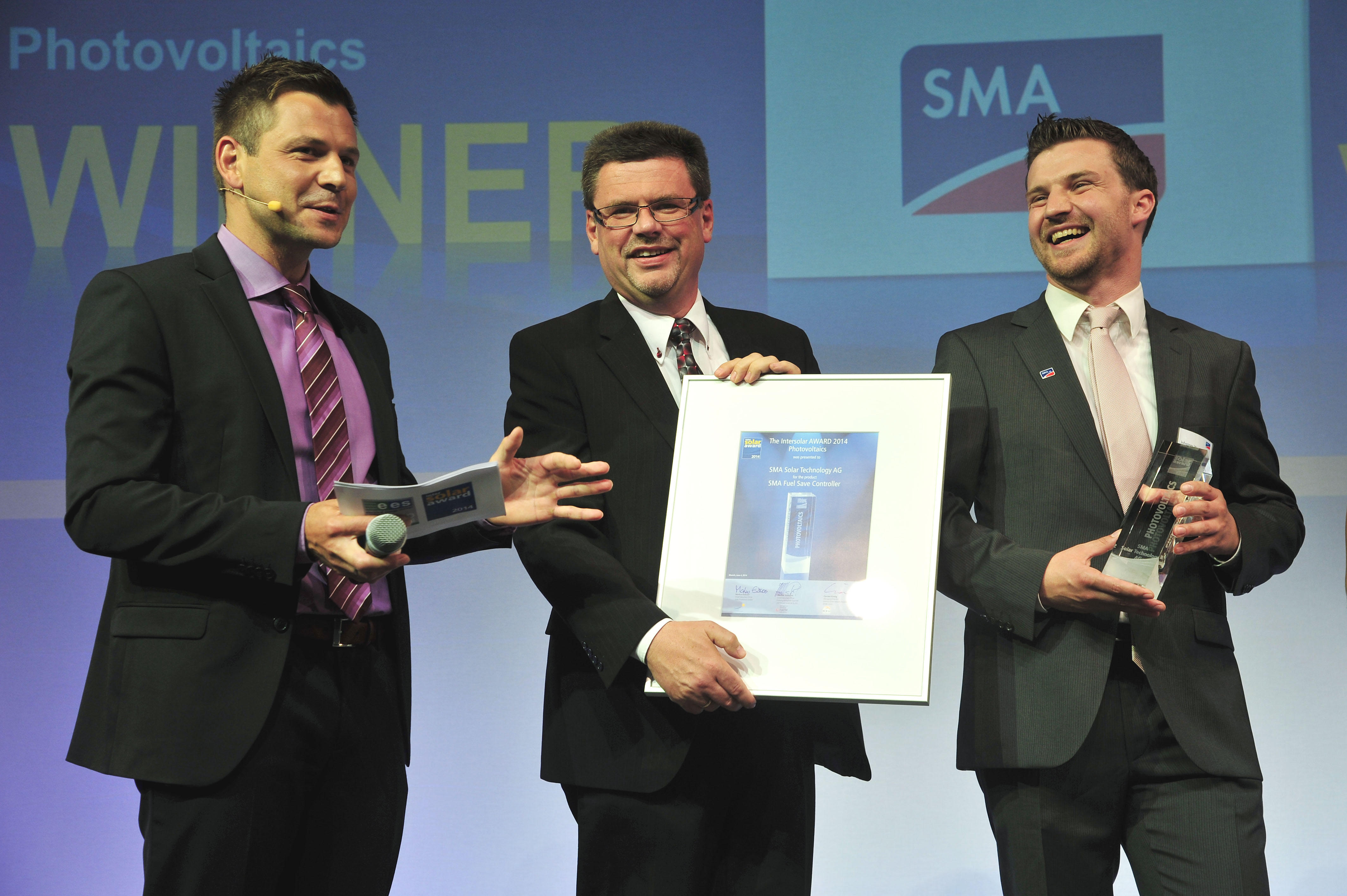 """Johannes Weide (right) and Volker Wachenfeld (middle) received the Intersolar AWARD in the """"Photovoltaics"""" category for the SMA Fuel Save Controller at Intersolar Europe 2014 in Munich."""