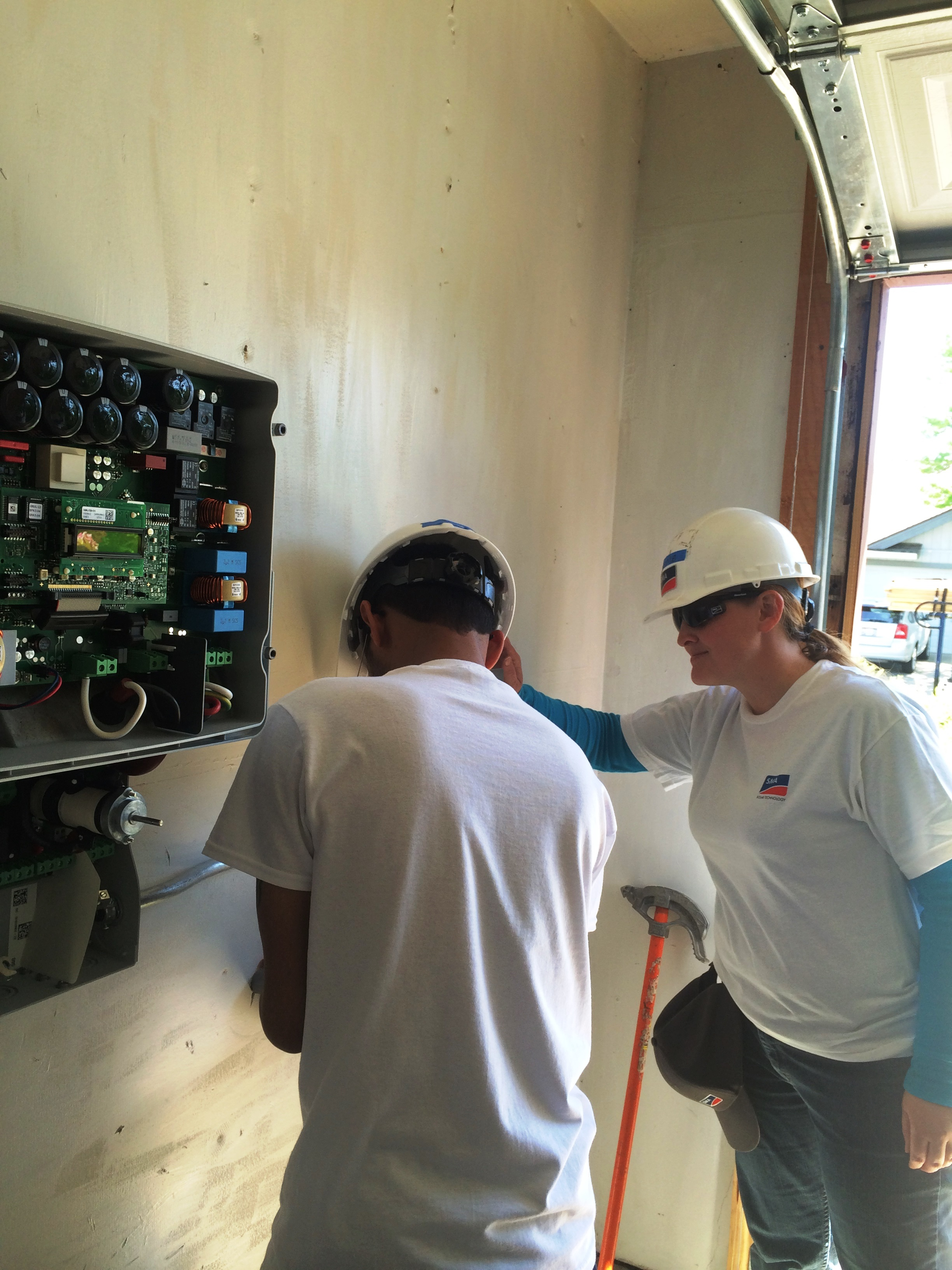 Myself on the right installing a Sunny Boy 3000-US with a colleague for GRID Alternatives.