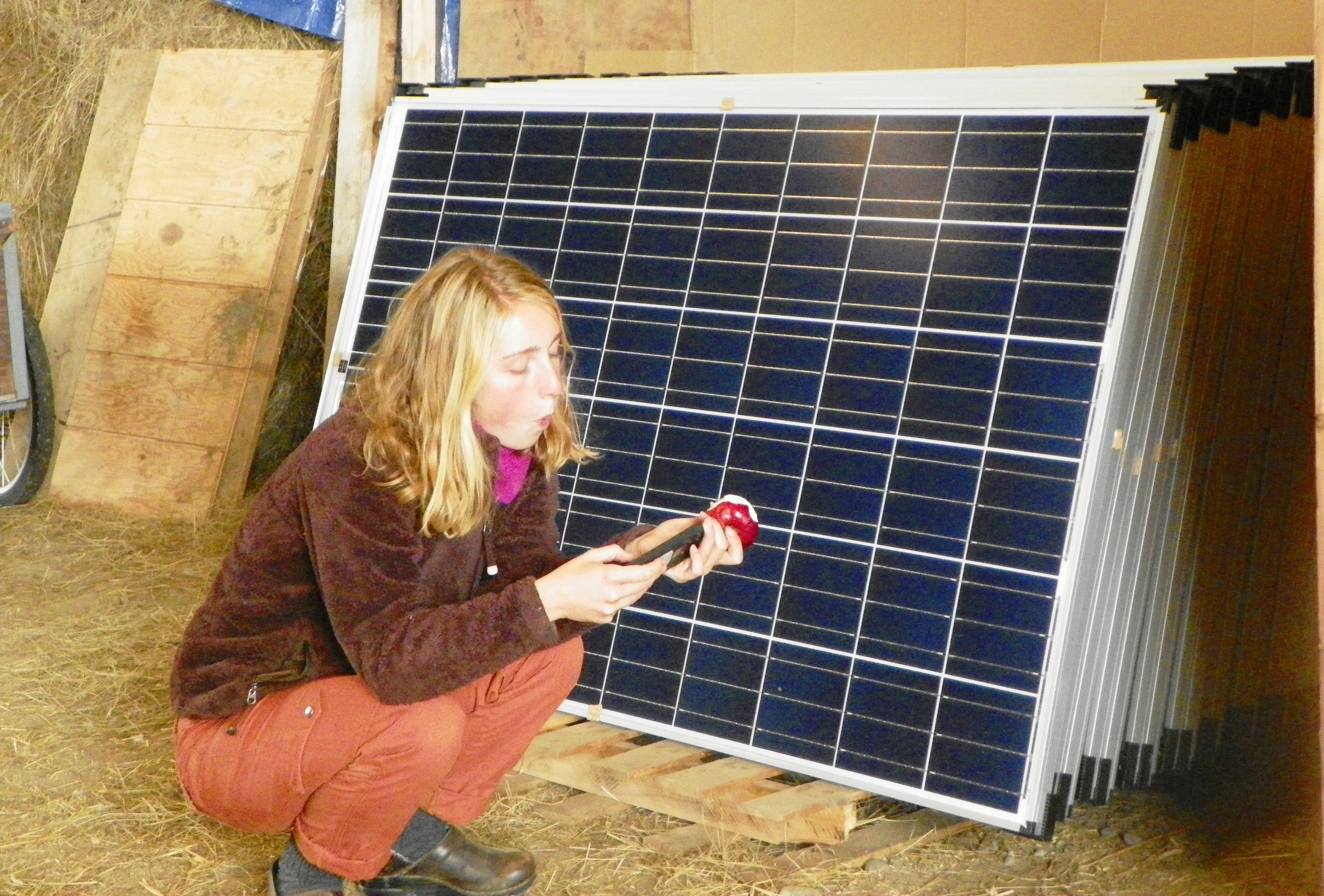 A student takes a break from the barn build next to the solar modules, waiting for installation.