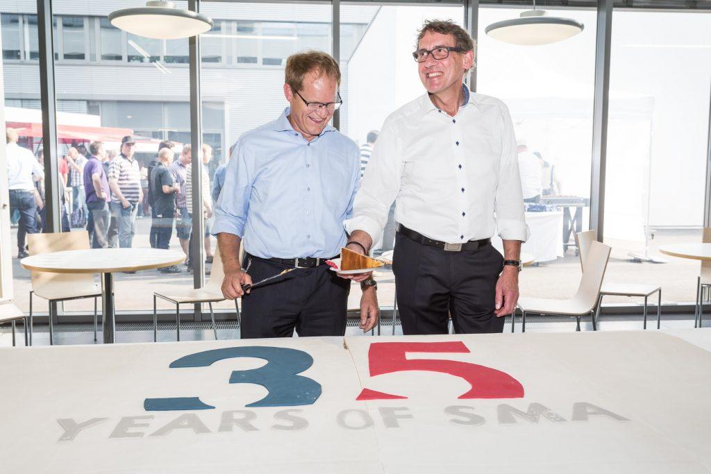 Die SMA Vorstände Jürgen Reinert (l.) und Roland Grebe schnitten den Geburtstagskuchen an.