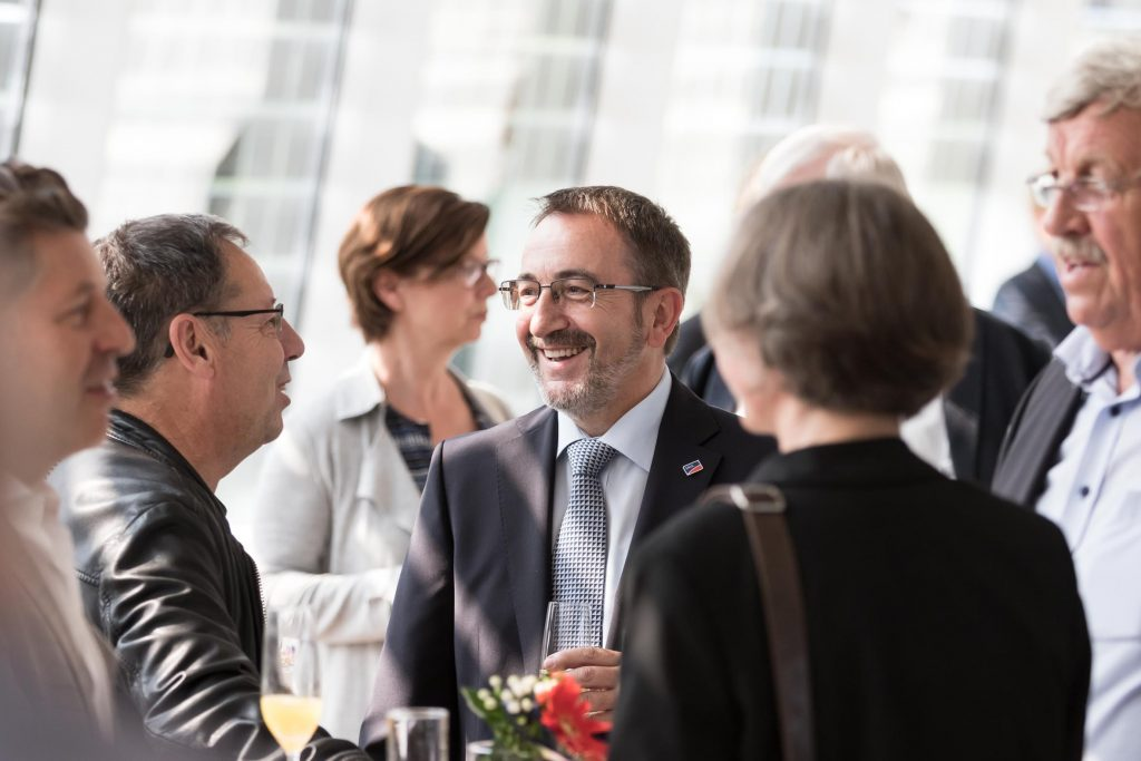 SMA Gründer Reiner Wettlaufer (M.) im Gespräch mit Gästen.